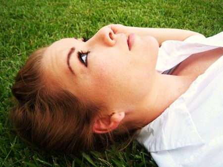 Young brunette lying in grass, looking at the sky photo