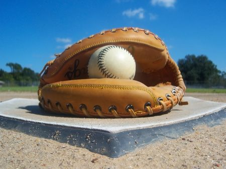 baseball field: A baseball and glove sitting on home plate, awaiting the team.