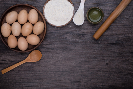 kitchen tool: Wooden background with baking ingredients (eggs, flour and rolling pin) over rustic texture. Top view. Space for text. Food or cooking concept.