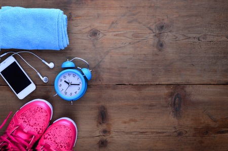 copy: Fitness and sport equipment : Measuring tape,mat.sneakers,towel,bottle of water with wooden background on top view Stock Photo