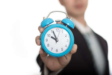 past midnight: man with an alarm clock in a hand. Isolated on white background Stock Photo