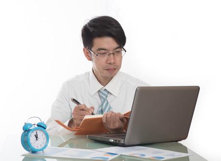 empleados trabajando: joven hombre de negocios de perforación loco de apagar el reloj de alarma sentado en el escritorio de oficina trabajando con el ordenador portátil en el concepto del proyecto y la fecha límite concepto de la tensión de negocio Foto de archivo