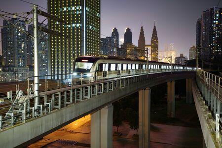At night, the light rail train shuttles through the city. Reklamní fotografie