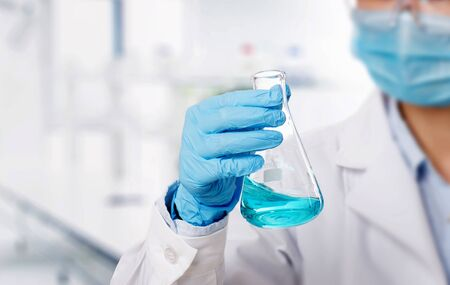 Laboratory beaker in analyst's hand in plastic glove