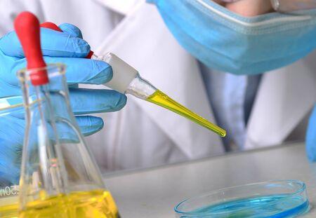 Laboratory beaker in analyst's hand in plastic glove Zdjęcie Seryjne - 124747467