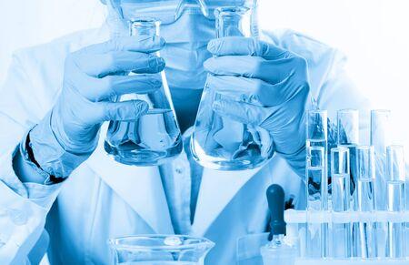 Laboratory beaker in analyst's hand in plastic glove Zdjęcie Seryjne - 124748556