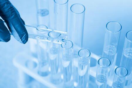 Laboratory beaker in analyst's hand in plastic glove Zdjęcie Seryjne - 124748557