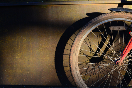 the fromt wheel with tire of the old bicycle with shadow on  metal panel and sunlight in evening