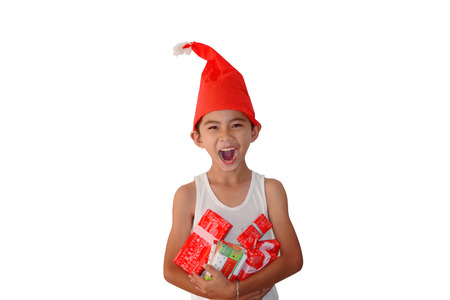 revelation: Happy revelation face of young  asian boy  wearing a hand madae santa claus hat and holding presents boxes on his chest with white background isolated Stock Photo