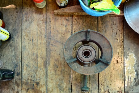 the old iron gas stove  with pan,bottles and food seasoning on wooden table Stock Photo