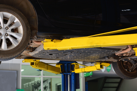 the blue lift post with yellow hands supported the car chassis in the repair shop