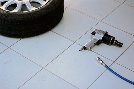 the metal wheel with tire  and air wrench with blue air line on grey tile at hte car repair shop 版權商用圖片