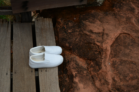 white shoes put on old wood floor at the walkway of nature park in Thailand