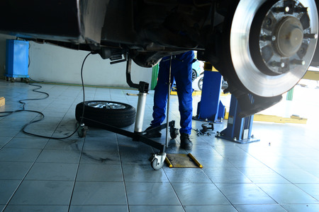 the legs of a mechanic in blue uniform and safety shoes  working under the car the  black wheel ,the electric wire and the tool on ground at the car repair shop