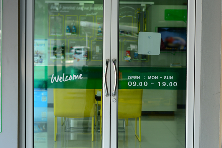 the glasses door with welcome letters and open time on green label at car repair shop