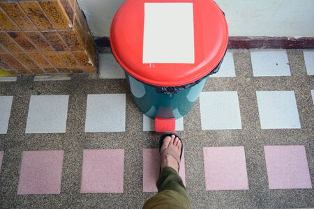 a right leg of a man steping on the orang button pad at the green bin on tile floor