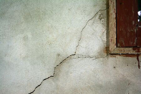 the small cracked on grey wall  near wooden  window in countryside of Thailand Stock Photo