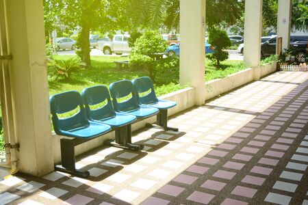 The row of blue seats at corridor in the building in the morning with yellow sunlight and many parked cars