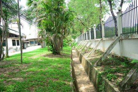 the  cement  vent  near the metal fence  with the trees  ,palms and grass behind the buildings