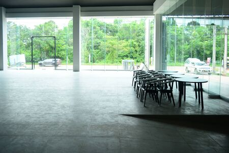 The empty  showroom after renovate with wooden chairs and tables with white bright light from outside Фото со стока