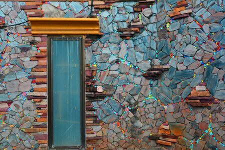 the colorful of old wall made from color stone cladding and a small window  at the local home in the northern of Thailand Фото со стока
