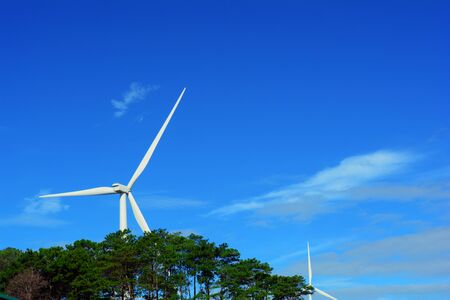 The white electric wind turbine with blue sky and trees  at Petchaboon,Thailand Фото со стока