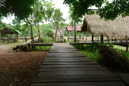The wooden bridge  connect to the empty huts at the tourist attraction on the dam coast at UdonThani ,Thailand Фото со стока