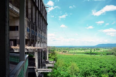 The unfinished buildings among the moutains and forest  with blue sky and white clouds Фото со стока