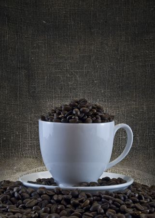 coffeebeans: white cup with coffee-beans on a dark background