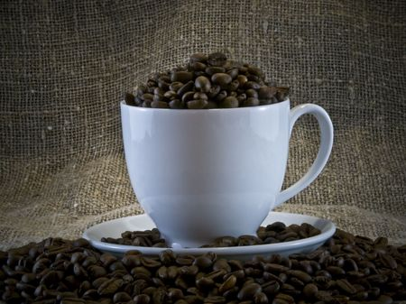 coffeebeans: white cup among fragrant coffee-beans