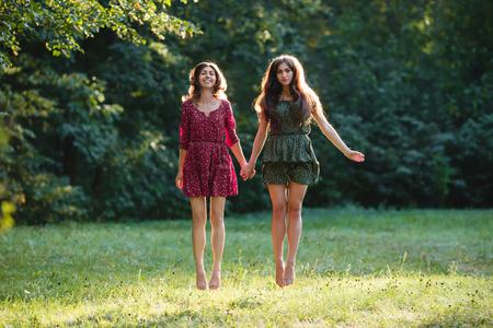 Dos, joven, sonriente, mujeres, levitar
