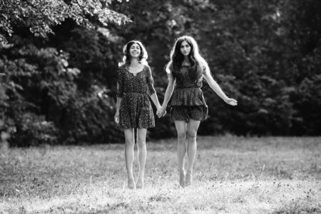 levitate: Two young smiling women levitate Stock Photo