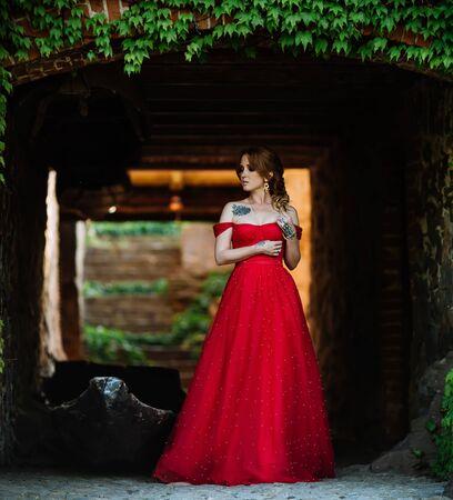 Rothaarige Frau im roten Kleid nahe dem Schloss