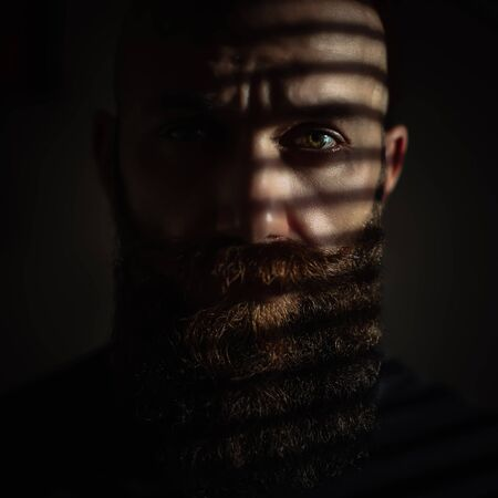 Close-up portrait of middle aged brutal bearded man with expressive eyes and striped shadows on his face with black background