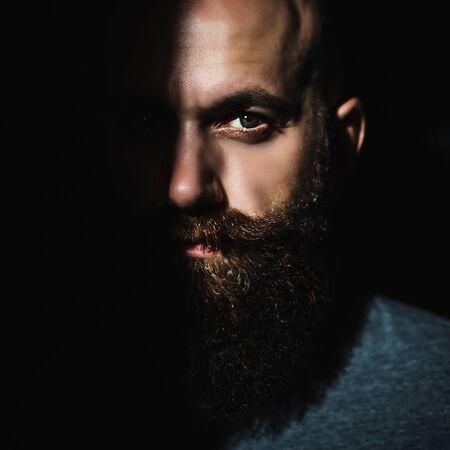 Close-up portrait of middle aged brutal bearded man with expressive eyes and shadow on half of his face with black background Imagens