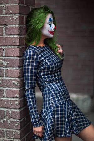 Portrait of a green haired girl in checkered dress with clown makeup on a brick wall background. Stok Fotoğraf