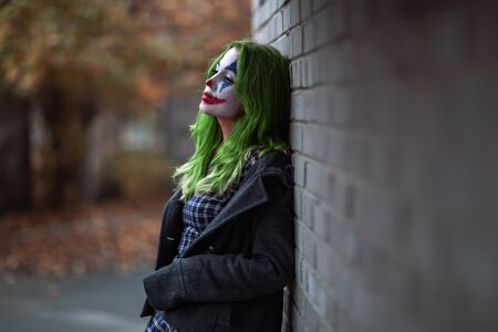 Portrait of a green haired girl in checkered dress with clown makeup on a brick wall background. Stock fotó