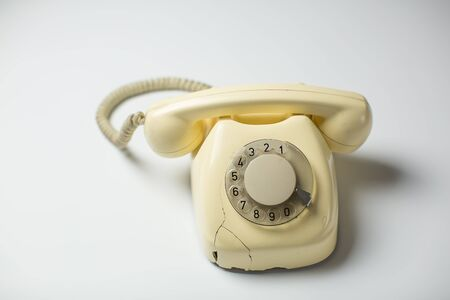 White retro rotary telephone with cracks and broken parts on white background Imagens - 138297739