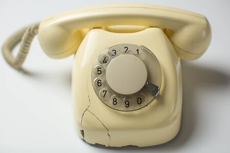 White retro rotary telephone with cracks and broken parts on white background