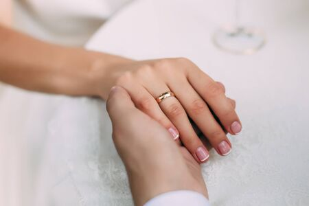 Groom holds brides hand with ring on her finger, close-up view