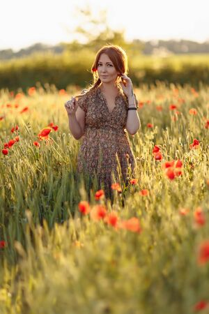 Redhead woman on green field with poppies Stock Photo