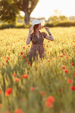 Rothaarige Frau mit Hut auf grünem Feld mit Mohnblumen Standard-Bild