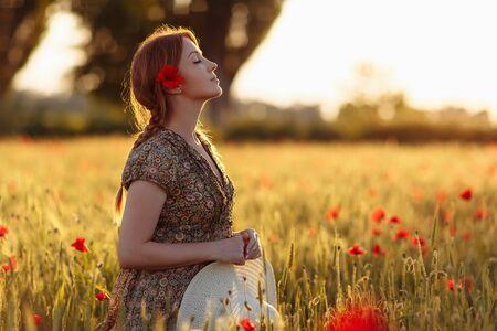 Roodharige vrouw met hoed op groen veld met klaprozen Stockfoto