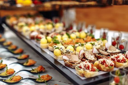 Different light snack on wooden tray on wedding party