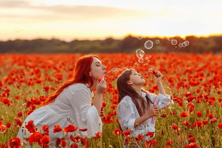 Little happy girl with redhead mother in white dresses blow bubbles on poppy field at warm summer sunset Stockfoto