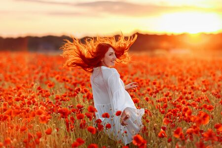 Happy redhead smiling woman in white dress on field of poppies at warm summer sunset 版權商用圖片