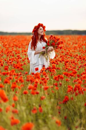 Portrait of beautiful redhead woman in wreath on green field with bouquet of poppies in summer sunset