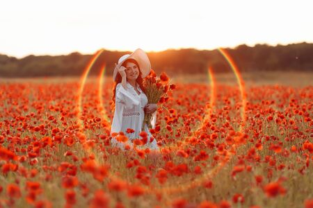 Beautiful smiling happy redhead woman in white hat on green field with bouquet of poppies in summer sunset 版權商用圖片