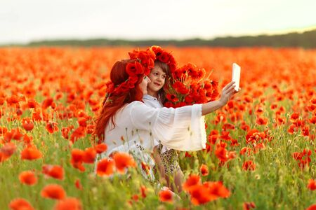 Little girl with redhead mother in white dresses and wreathes make selfie with bouquet of poppies on poppy field at warm summer sunset