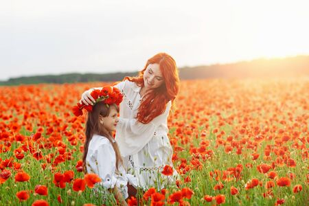 Little happy girl with redhead mother in white dresses makes wreath on poppy field at warm summer sunset 版權商用圖片
